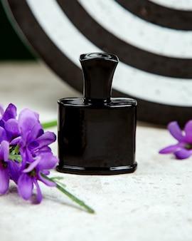 Garrafa preta de perfume em cima da mesa