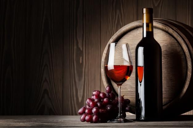 Garrafa preta e copo de vinho tinto com uvas e barril
