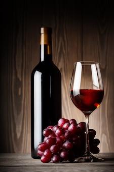 Garrafa preta e copo de vinho tinto com uvas