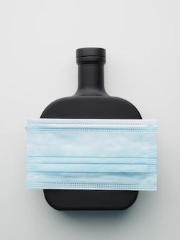 Garrafa preta e de bebida alcoólica com máscara protetora.