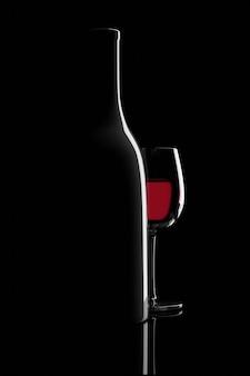 Garrafa retroiluminada e copo de vinho tinto isolado no preto.