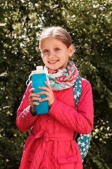 Garrafa reutilizável de silicone nas mãos de uma menina em uma área verde