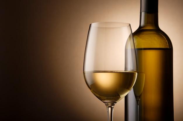 Garrafa sem rótulo e copo de vinho branco no gradiente de ouro