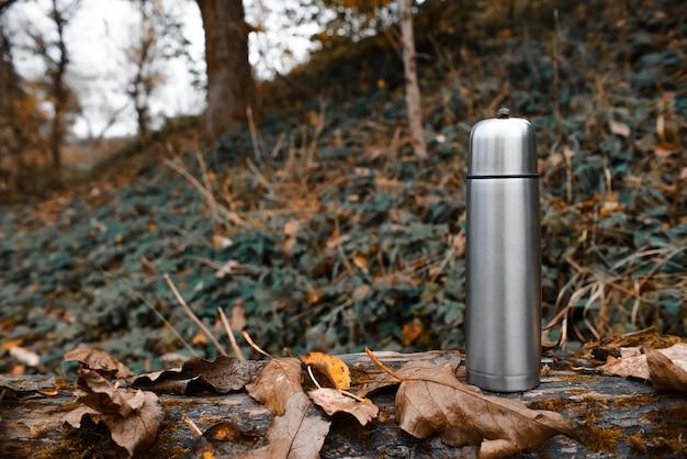 Garrafa térmica a vácuo de metal na floresta