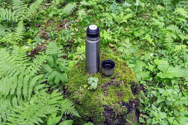 Garrafa térmica aberta de aço inoxidável com bebida de chá no toco em floresta de coníferas