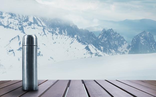 Garrafa térmica com chá ou café e paisagem de montanhas no fundo. bebida quente na mesa de madeira com céu nevado e nublado. quente no dia de inverno, feriados, viagens, ano novo e época do natal.