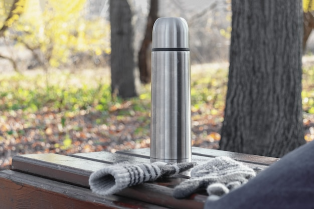 Garrafa térmica com chá quente ou café em um banco no parque outono