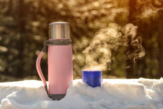 Garrafa térmica com uma caneca fumegante de bebida quente fica na neve.