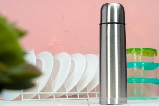 Garrafa térmica contra utensílios de mesa em uma cozinha