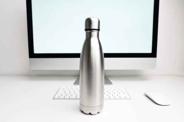 Garrafa térmica de aço para água na mesa do escritório perto do computador e documentos