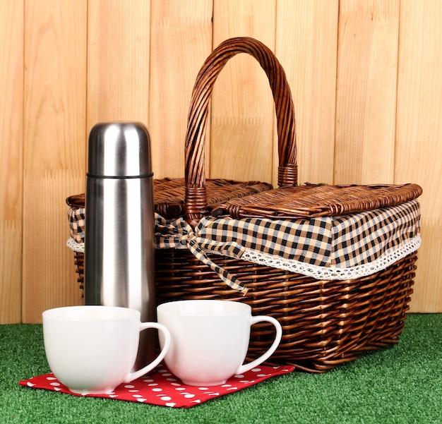 Garrafa térmica de metal com xícaras e cesta na grama em uma superfície de madeira