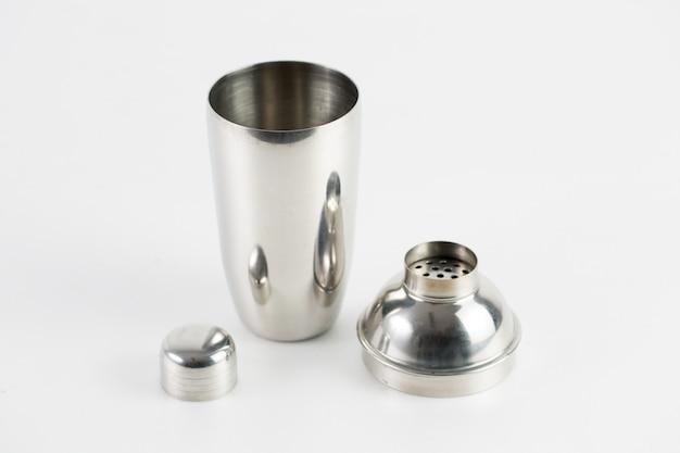 Garrafa térmica de metal prata com três peças isoladas em uma parede branca