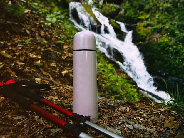 Garrafa térmica e bastões de caminhada em um fundo natural desfocado com cascata