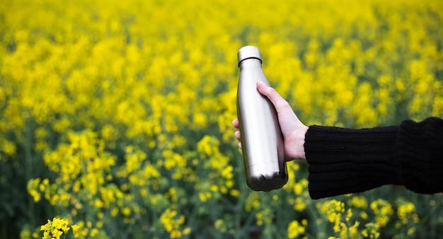 Garrafa térmica inoxidável na mão, na superfície do campo de colza.