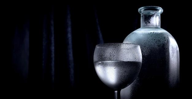Garrafa transparente de vodka ou álcool com um copo shot