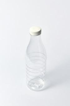 Garrafa vazia de plástico transparente para produtos lácteos, água e outros líquidos com um copo branco sobre um fundo cinza claro. copie o espaço.