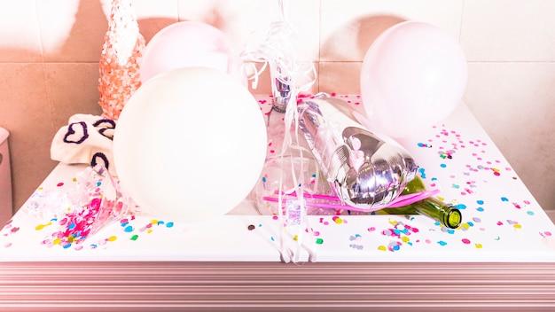 Garrafa verde com confete e balões brancos