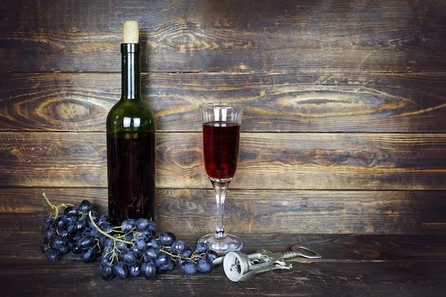 Garrafa verde escura e copo de vinho transparente com vinho tinto e cacho de uvas na superfície da prancha de madeira marrom, saca-rolhas nas proximidades