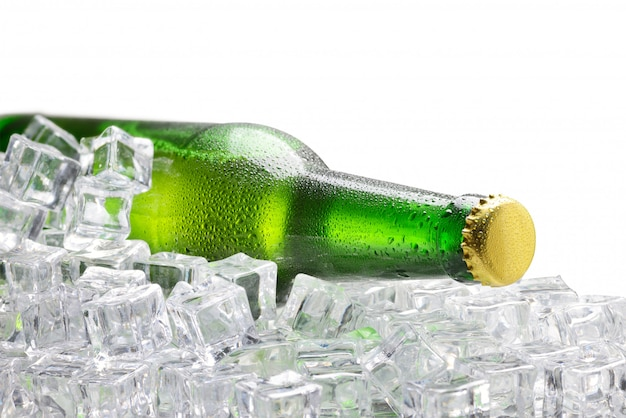 Garrafa verde fria de cerveja sobre os cubos de gelo, isolado no fundo branco