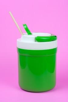 Garrafa verde para a água fria no fundo cor-de-rosa.