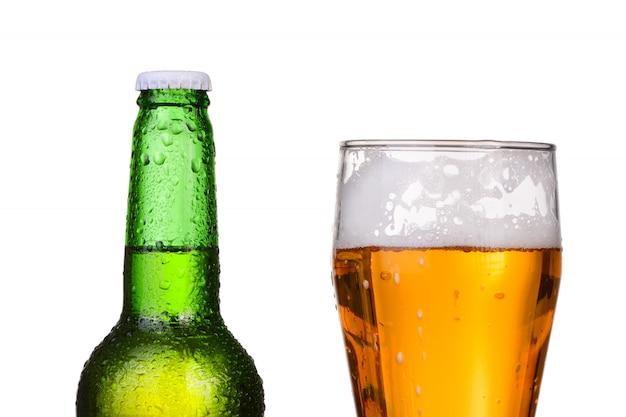 Garrafa verde refrigerada com condensado e um copo de cerveja em fundo branco isolado