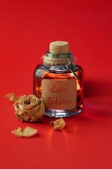 Garrafa vintage com poção do amor mágica e rosa seca no espaço vermelho