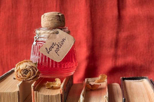 Garrafa vintage com poção mágica do amor em livros de feitiços contra tecido vermelho, espaço para texto