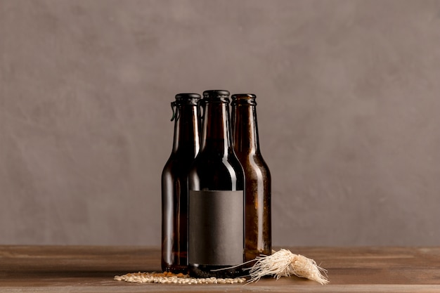 Garrafas alcoólicas marrom no rótulo cinza na mesa de madeira