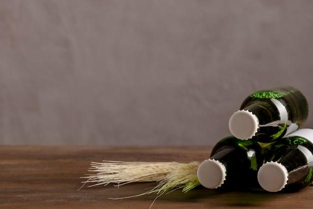 Garrafas alcoólicas verdes em rótulo branco na mesa de madeira
