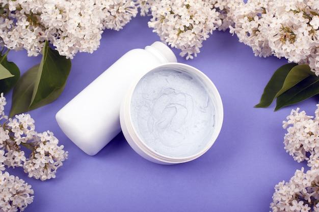 Garrafas brancas com cosméticos para cuidados com a pele com as flores lilás brancas no close-up violeta do fundo.