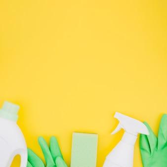 Garrafas brancas com luvas verdes e esponja em pano de fundo amarelo
