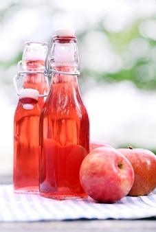 Garrafas com bebidas vermelhas e algumas maçãs