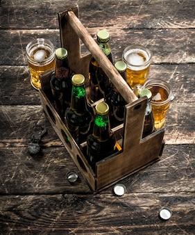 Garrafas com cerveja em uma velha caixa com copos