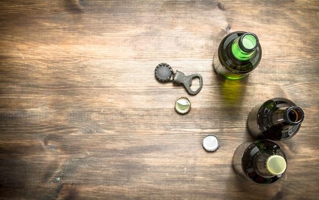 Garrafas com cerveja fresca, abridor e rolhas em mesa de madeira