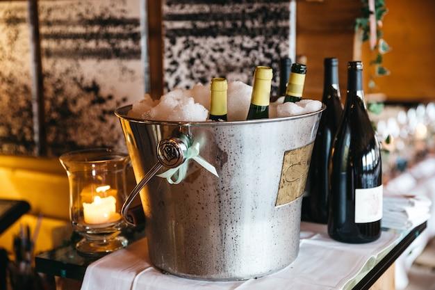Garrafas com champanhe estão esfriando no balde com gelo e garrafas com vinho estão próximas