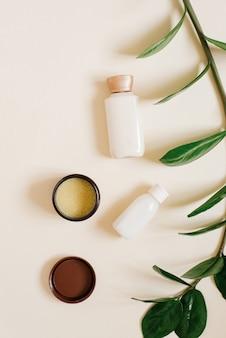 Garrafas com creme corporal ou facial, manteiga de cacau sólida em uma jarra aberta e um ramo de uma planta tropical em bege
