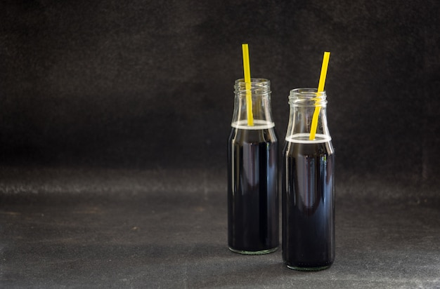 Garrafas com desintoxicação carvão ativado preto limonada na mesa