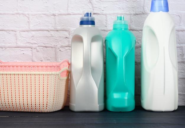 Garrafas com detergente líquido e cestos de roupa vazios de plástico em uma mesa de madeira azul. superfície de parede de tijolo branco