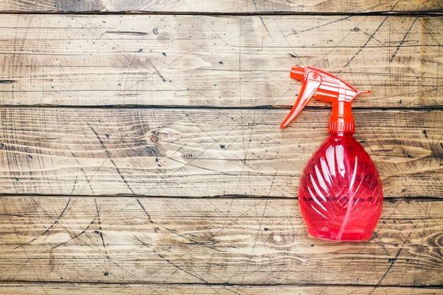 Garrafas com detergentes e produtos de limpeza no fundo de madeira.