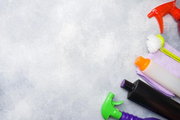 Garrafas com detergentes, escovas e esponjas no fundo concreto.