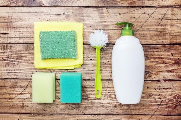 Garrafas com detergentes, escovas e esponjas no fundo de madeira.