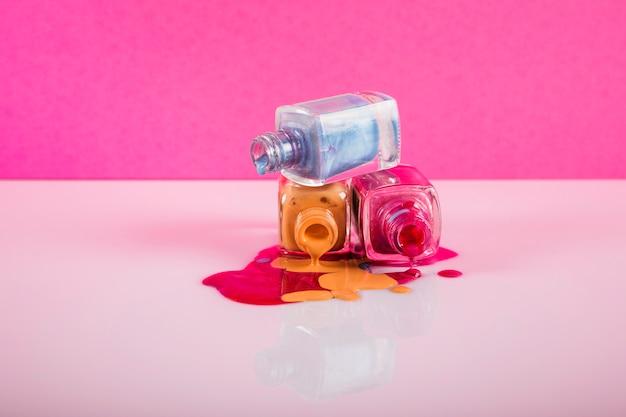 Garrafas com esmalte derramado sobre fundo colorido