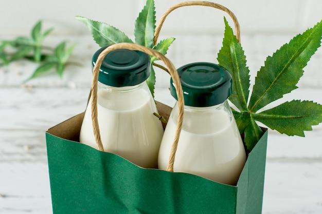 Garrafas com glúten vegan de ervas cannabis e leite sem lactose e folhas de cannabis na mesa de madeira.
