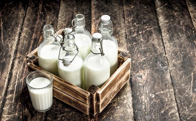 Garrafas com leite fresco em uma caixa na mesa de madeira.