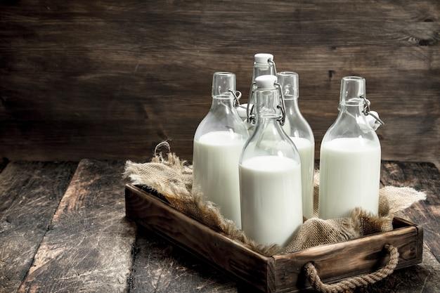 Garrafas com leite fresco em uma caixa. sobre um fundo de madeira.