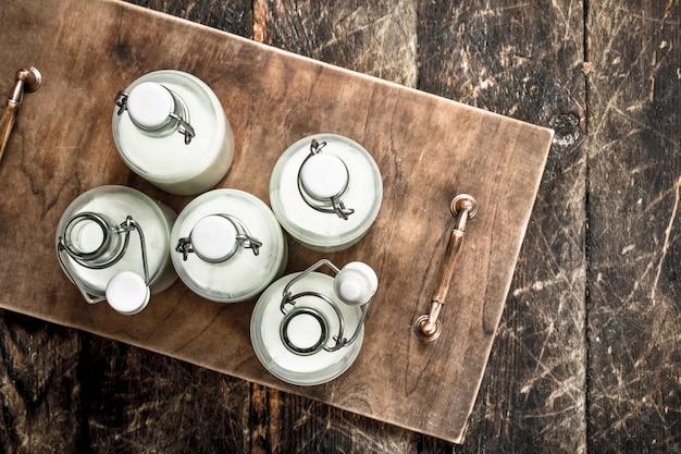 Garrafas com leite fresco na mesa de madeira.
