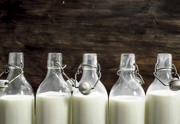 Garrafas com leite fresco. sobre um fundo de madeira.