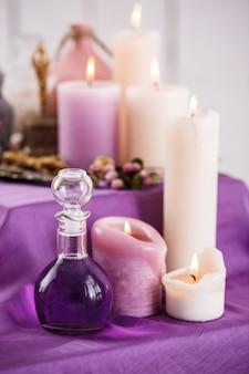 Garrafas com óleo essencial de aroma e velas aromáticas. configuração de spa