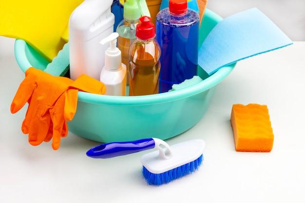 Garrafas com produtos químicos domésticos para limpeza de apartamento em bacia de plástico verde. escove e esponja na mesa. fundo branco.