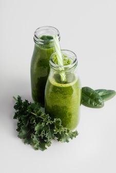 Garrafas com smoothie verde de ângulo alto